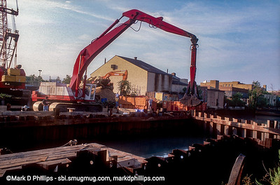 """A backhoe dredges the bottom of the Gowanus Canal in an enclosed area by the Union Street Bridge in 1999. Sewage flowed into the canal as early as 1858, and by the 1880's the waterway had gained the moniker """"Lavendar Lake"""" for its odorous qualities. The current cost of the overall EPA Superfund cleanup plan is estimated to be over $1.5 billion, and the entire project won't be completed until mid-2023."""