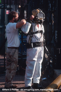 Diver prepares to enter  the Gowanus Canal during the city-led 1999 cleanup effort that involved repairs to the flushing tunnel and a partial dredging at the head of the waterway. The results were immediate with an increase in fish and wildlife. The divers had challenging conditions, coming out covered in oil and tar and working conditions with no visibility underwater.