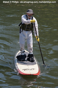 A paddle boarder wears sealed garbage bags on his feet, an enviro suit, and heavy gloves as protection from the water during The Gowanus Challenge on the Gowanus Canal in Brooklyn in 2014. The yearly race is sponsored by the Gowanus Dredgers, a canoeing organization that is one of the biggest proponents for cleaning the waterway.
