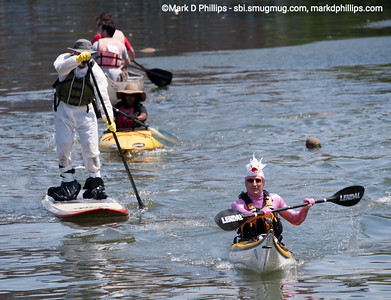 Todd Seidman of Dolphin Rising (right) paddles his kayak ahead of a paddle boarder wearing protective clothing as they compete in the Gowanus Challenge on the Gowanus Canal in Brooklyn in 2014. The yearly race is sponsored by the Gowanus Dredgers, a canoeing organization that is one of the biggest proponents for cleaning the waterway.