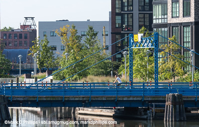 A bike rider crosses the Carroll Street Bridge by the new condos on the western bank. As the EPA Superfund project continues, new construction will continue.