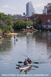 Tim Gamble and his wife, Kate Holmes, wear shark outfits for their team, Combined Shark Overflow, as they compete in the Gowanus Challenge on the Gowanus Canal in Brooklyn in 2014. The yearly race is sponsored by the Gowanus Dredgers, a canoeing organization that is one of the biggest proponents for cleaning the waterway. Looking up canal toward Carroll Street, the canal looked wild.