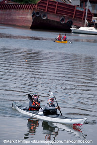 Tim Gamble and his wife, Kate Holmes, wear shark outfits for their team, Combined Shark Overflow, as they compete in the Gowanus Challenge on the Gowanus Canal in Brooklyn in 2014. The yearly race is sponsored by the Gowanus Dredgers, a canoeing organization that is one of the biggest proponents for cleaning the waterway, including the abandoned barge in the background.