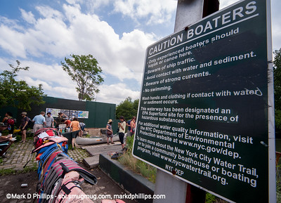 The Gowanus Challenge, a canoe race on the Gowanus Canal in Brooklyn, before the Gowanus Dredgers had their boathouse in the new condo building that would take over this site. The warning sign stressed everything wrong with the Gowanus Canal in 2014.