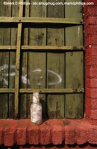 Bottle sits on boarded window by Gowanus Canal in Brooklyn, NY