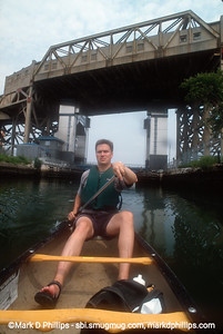 Owen Foote, one of the founders of the Gowanus Dredgers Canoe Club, paddles on the Gowanus Canal with the Ninth Street Subway station looming above. The 1.7 mile long canal is currently in an EPA Superfund cleanup plan that is estimated to be over $1.5 billion, and the entire project won't be completed until mid-2023. The Gowanus Canal is located in one of the densest population centers in America.
