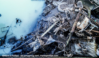 At Low tide during 1998, metal garbage is uncovered by the Carroll Street Bridge of the Gowanus Canal in Brooklyn, NY. The aea was cleaned out during the during the city-led 1999 cleanup effort that involved repairs to the flushing tunnel and a partial dredging at the head of the waterway. The results were immediate with an increase in fish and wildlife. The divers had challenging conditions, coming out covered in oil and tar and working conditions with no visibility underwater.