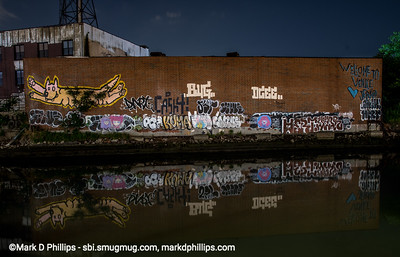 """Nighttime shots along the Gowanus Canal by Carroll Street bridge. Since 2016, the patch of graffiti on a warehouse by the Carroll Street Bridge on the bank of the Gowanus Canal welcomed visitors with the tagline 'Welcome to Venice' with the signature """"Love Jerko."""" But just like the Canal itself, it became a victim of gentrification. The former home of Alex Figliolia Water & Sewer, the 65,000-square-foot industrial building disappeared without a trace. On my first visit to the canal since the pandemic struck, I had one of those """"Oh No"""" moments when I drove across the historic Carroll Street Bridge and realized the graffiti covered wall was gone. Not just gone but obliterated like it had never been there."""