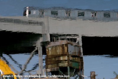 A subway train is reflected in the water of the Gowanus Canal. The EPA begins dredging the Gowanus Canal on November 18, 2020, during the COVID-19 pandemic, by the Carroll Street Bridge. The current cost of the overall EPA Superfund cleanup plan is estimated to be over $1.5 billion, and the entire project won't be completed until mid-2023. The Gowanus Canal is located in one of the densest population centers in America.