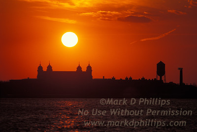 Sunset over Ellis Island with red sky and sun reflecting on New York Harbor.