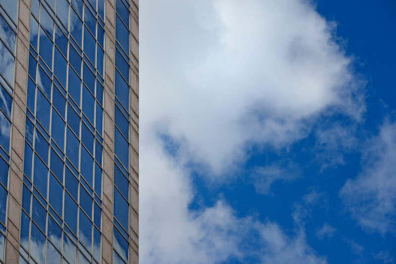 Windows reflecting blue sky and clouds next to a skyscraper in Manhattan, New York City