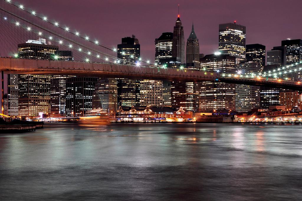 New York City Financial District and Brooklyn Bridge At Night.
