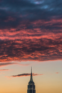 Fluffy pink clouds loom over Empire State Building  at sunset