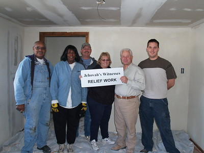 Workers helping with the inside of a damaged home