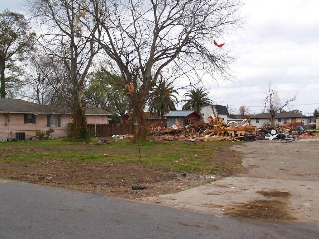 If we turn our attention directly across the street from the damaged houses we see a lot with a damaged house in the back ground.