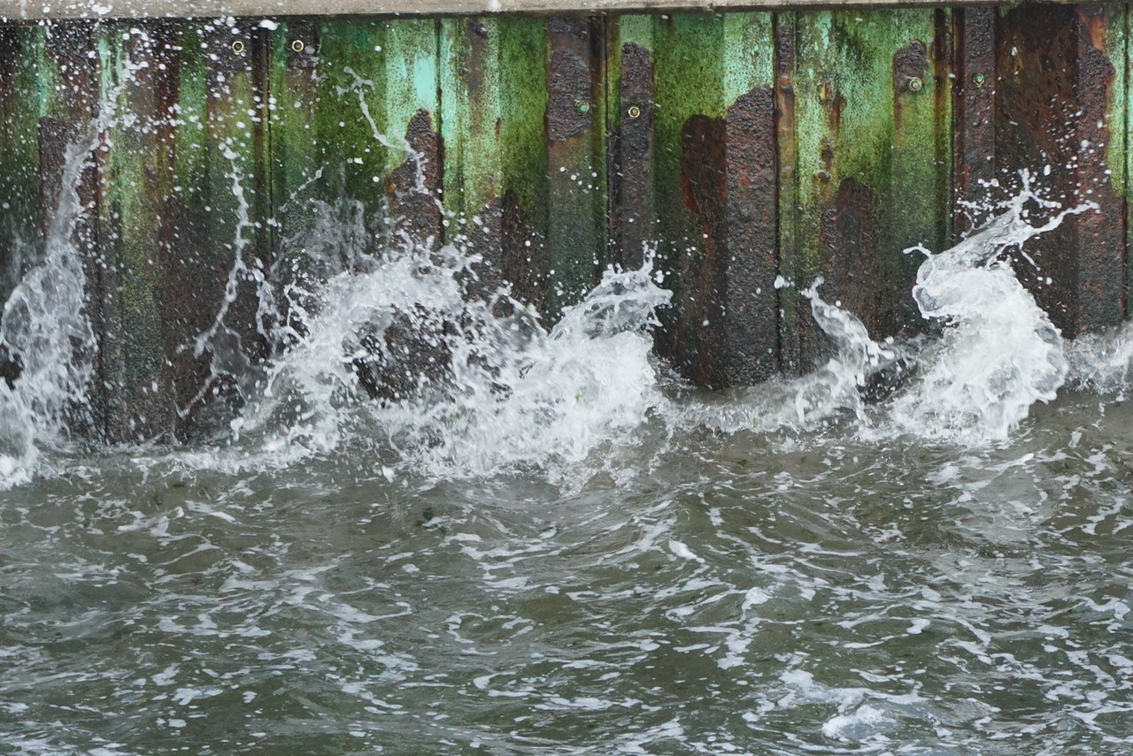 Splash against the rusted pier wall.