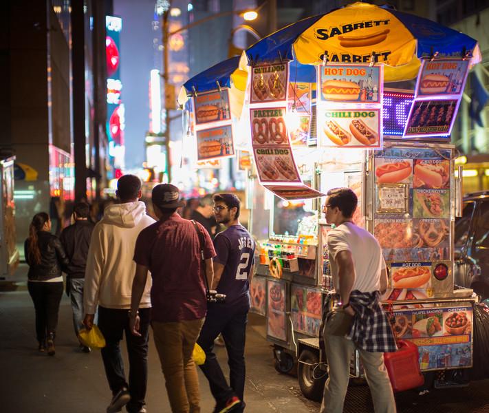 young men walking past Sabrett cart Times Square
