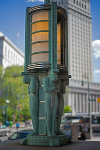 bronze deco men holding up lamp state building