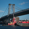 barge pushed by tug under Williamsburg Bridge