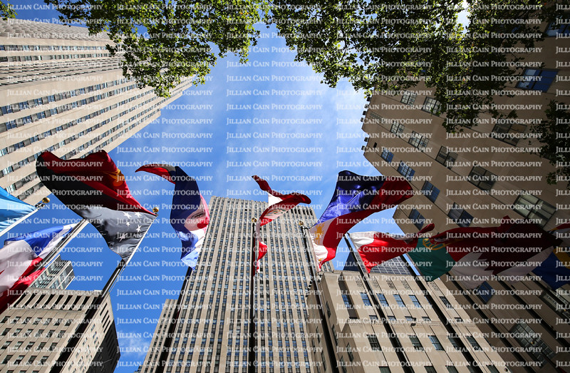 Looking up at the flags of Rockafeller Center in Manhattan, New York.