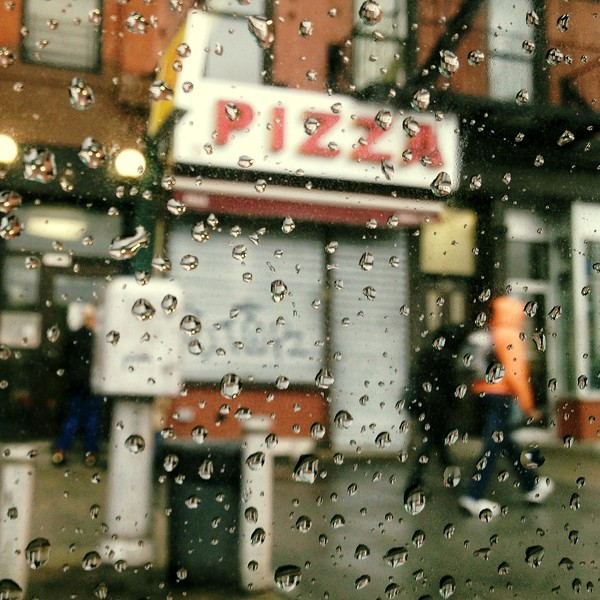 Pizza through a wet bus window. 2013.