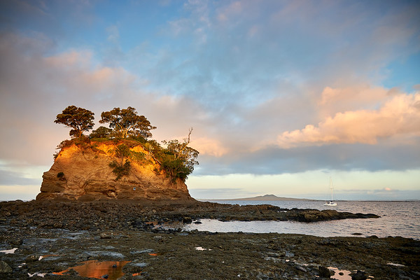 The last rays of sunshine catch The Tor at Waiake beach in Torbay. The rock gives the Auckland North Shore suburb its name