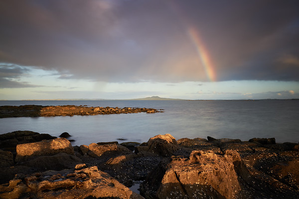 Looking towards Rangitoto Island, with passing rain clouds and rainbow in Auckland's Hauraki Gulf