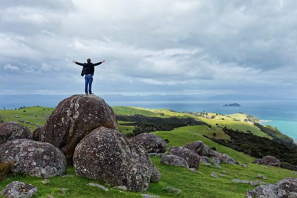 Man on a boulder enjoying the  splendour of Waiheke Island at Stony Batter Scenic Reserve