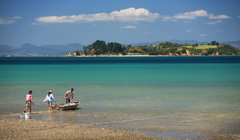 Family launching rowing boat, Waiheke Island, Hauraki Gulf