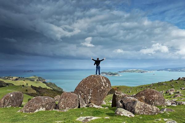 Man on a boulder enjoying the scenic splendour of Waiheke Island at Stony Batter Scenic Reserve