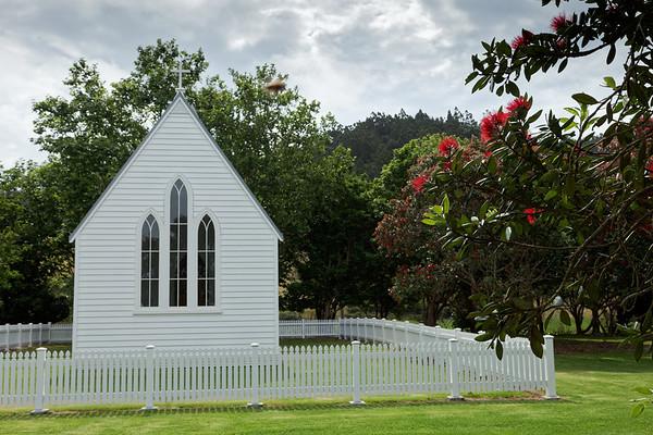 Church at Man O' War Bay with pohutukawa blossoms on Waiheke Island in the Hauraki Gulf