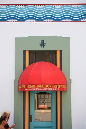 Modern couple walk past an Art Deco Tandoori restaurant in Napier
