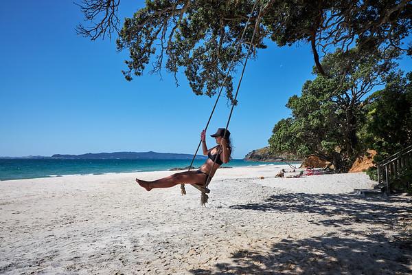 Girl on tree swing at Otama beach on the Coromandel Peninsula in New Zealand's North Island