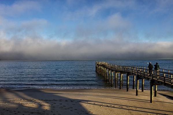 Morning sun breaks through the fog on a Hokianga jetty in Northland