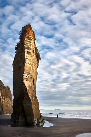 The Three Sisters rock formations dwarf a walker at Tongaporutu Beach on the Taranaki coast in New Zealand's North Island