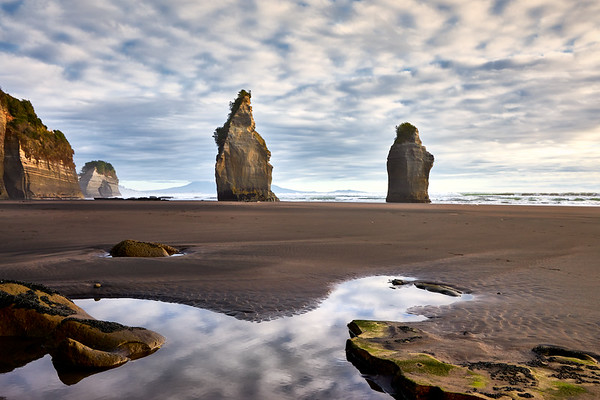 The Three Sisters rock formations over rockpool  at Tongaporutu Beach on the Taranaki coast in New Zealand's North Island