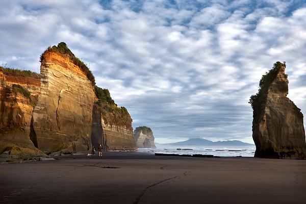 Walkers at the Three Sisters rock formations  at Tongaporutu Beach loking towards Mt Taranaki, in cloud, on the Taranaki coast in New Zealand's North Island