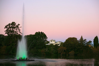 Coloured fountain in Victoria Park's lake at dusk, with fine home, in Wanganui