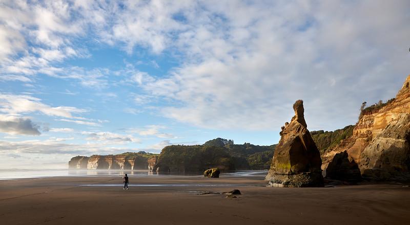 Walker at The Three Sisters rock formations  at Tongaporutu Beach on the Taranaki coast in New Zealand's North Island