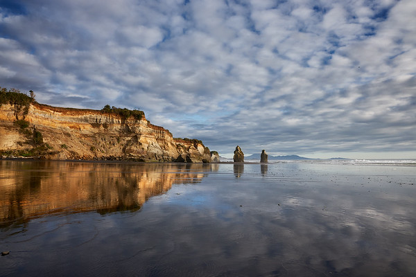 The Three Sisters rock formations with cliffs and refelections at Tongaporutu Beach on the Taranaki coast in New Zealand's North Island