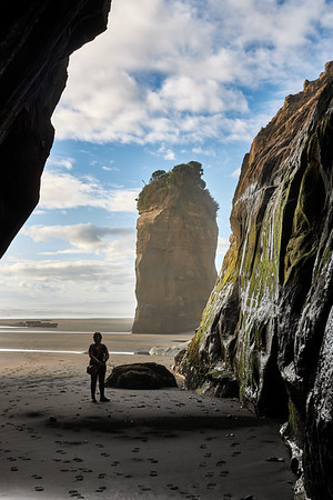 Girl at the mouth of a cave at the Three Sisters rock formations  at Tongaporutu Beach on the Taranaki coast in New Zealand's North Island
