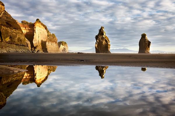 Reflections of The Three Sisters at Tongaporutu Beach on the Taranaki coast in New Zealand's North Island