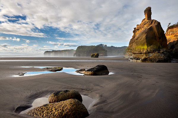 Lowview over rock pools of rock formations and cliffs at Tongaporutu Beach on the Taranaki coast in New Zealand's North Island