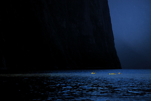 Kayakers dwarfed on Milford Sound in Fiordland National Park