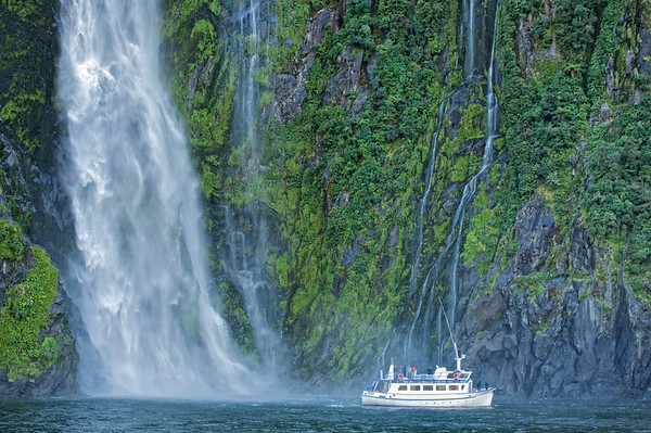 Tour boat at waterfall, Milford Sound, Fiordland National Park
