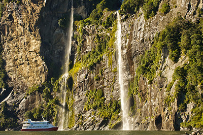 Waterfall at Milford Sound with tourboat, Fiordland National Park