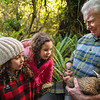 DSC_954  Haast tokoeka (Apteryx australis australis) Peter Hayden holds a 4 month old juvenile tokoeka captured for weighing as part of captive monitoring program, while Rahwa and Grace Steel look on. Photographed at Orokonui Eco-sanctuary for Predator Free 2050 Ltd *