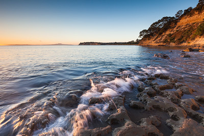 Water laps against eroded sandstone foreshore at sunrise. Rangitoto Island in background. Grannys Bay, Long Bay Regional Park, Auckland.