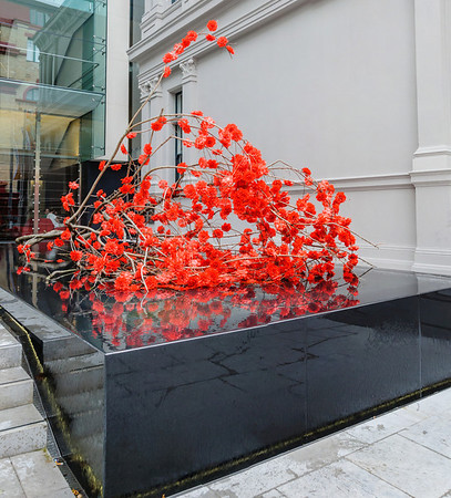 Artificial red blossoms resting on top of water fountain Auckland Art Gallery