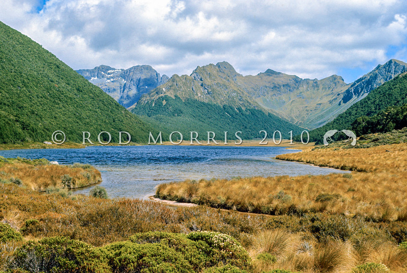 11001-51512  Lake Orbell (also known as Wai-o-Pani or 'lake of the friendless') in Takahe Valley. This same area was considered by Herries Beattie to be the place Ngatimamoe knew as Kohaka takahea. Murchison Mountains, Fiordland *